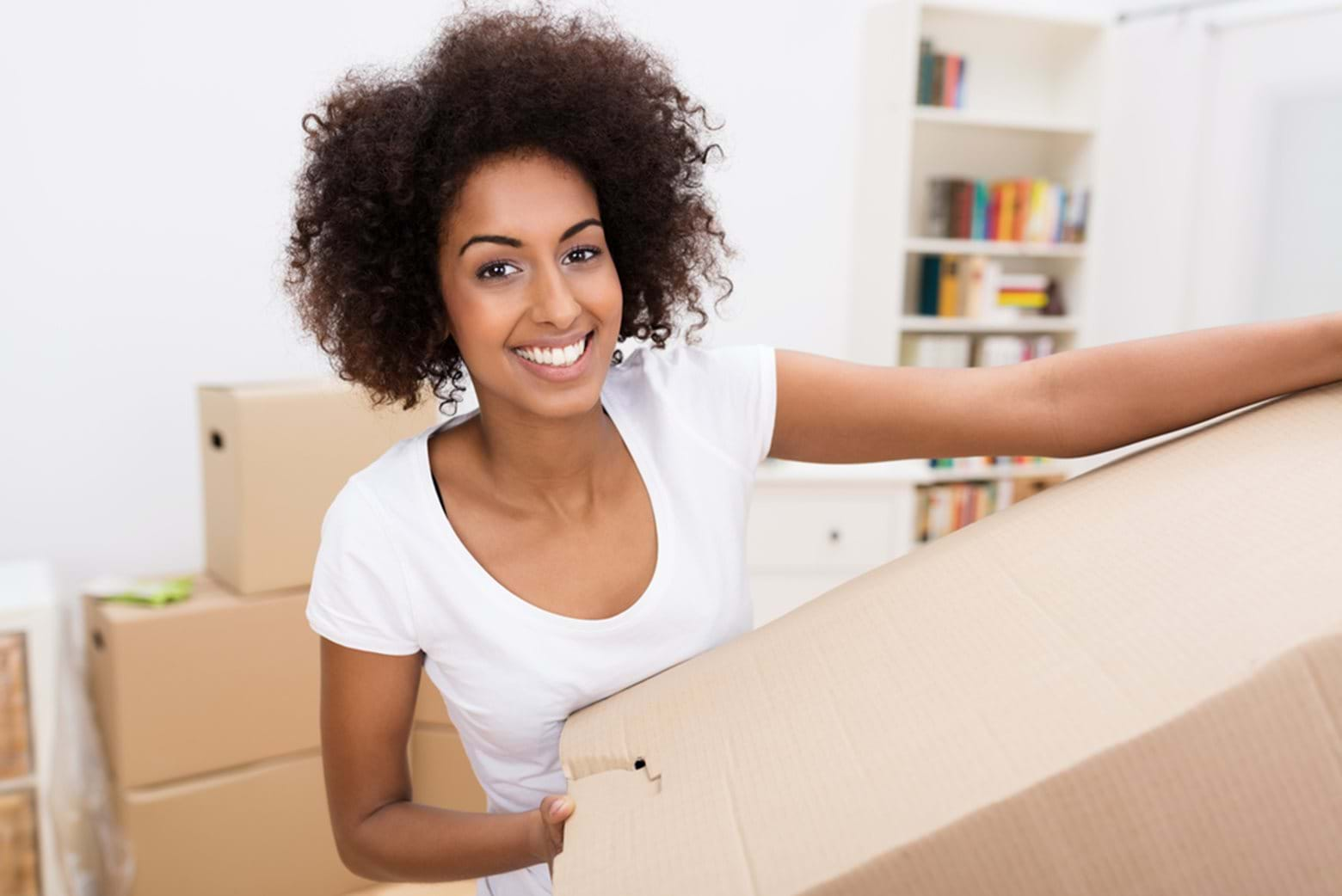 Smiling young woman carrying a cardboard box